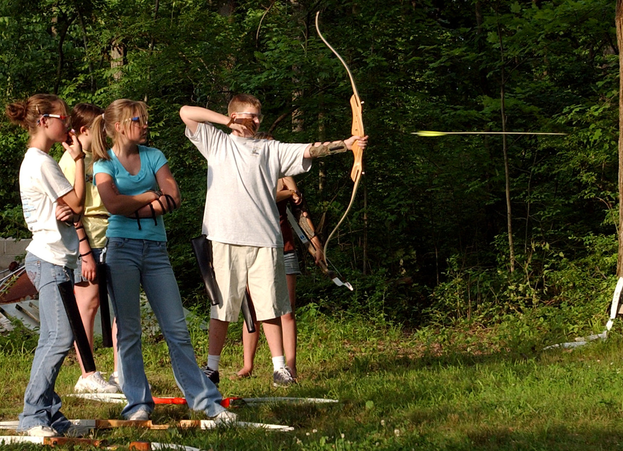 John King releases an arrow as twins Katie and Jenny Shaw, 14, watch in the scoring round for 4-H competition at the Hamilton Sportsman Club Wednesday, 06/28/06. Staff photo by E.L. Hubbard