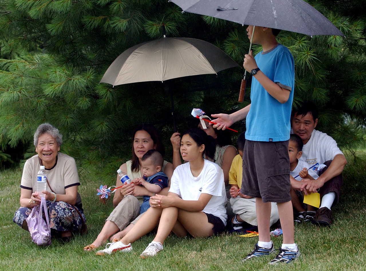The Peng((cq)) family, from Liberty Township, and Luong((cq)) family, from Monroe, seek shelter from the rain under some pines during the 4th of July Festival Parade Tuesday, 07/04/06. Staff photo by E.L. Hubbard