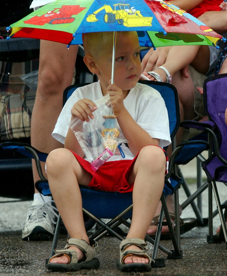 Garrett Day((cq)), 4, watches the 4th of July Festival Parade from the front row while holding an umbrella to keep dry Tuesday, 07/04/06. Staff photo by E.L. Hubbard