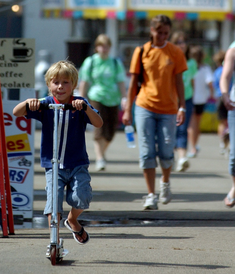 Braxton Moore((CQ)), 5, from Lancaster((CQ)), rides his scooter around the grounds of the Butler County((CQ)) fair Friday, 07/06/06. Braxton was spending the week at the fair, as his father operated the arcade. Staff photo by E.L. Hubbard