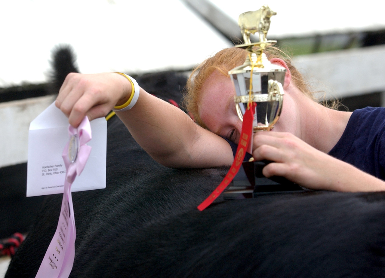 An exhausted Christa Lierer holds her trophy and ribbon from showmanship judging at the Butler County fair Wednesday, 07/26/06. The event was the last for Christa at this years fair. Staff photo by E.L. Hubbard