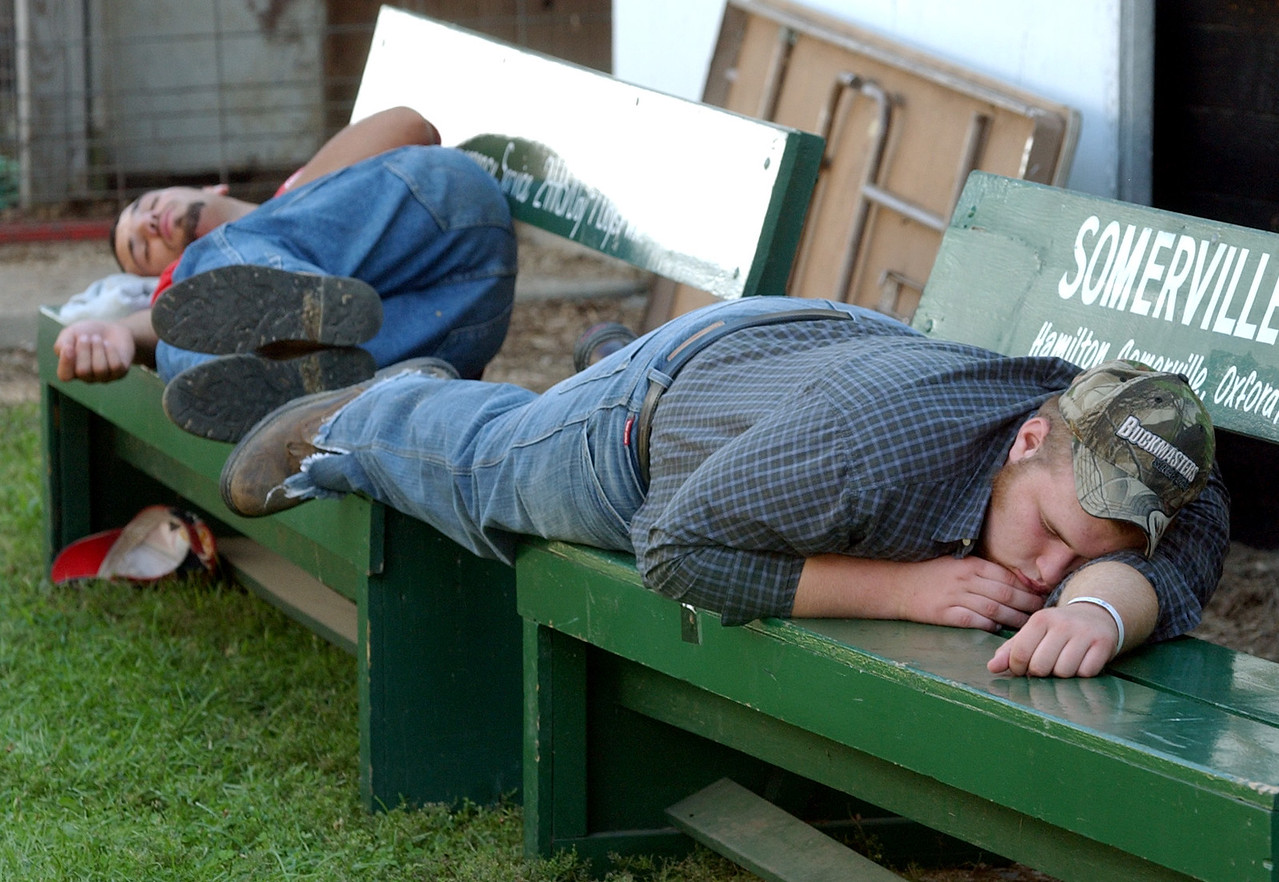 Mike Sullivan, front, and Josh Pruitt, both Fairfield residents, catch some shut-eye on two benches between barns at the Butler County fair Tuesday, 07/25/06. Staff photo by E.L. Hubbard