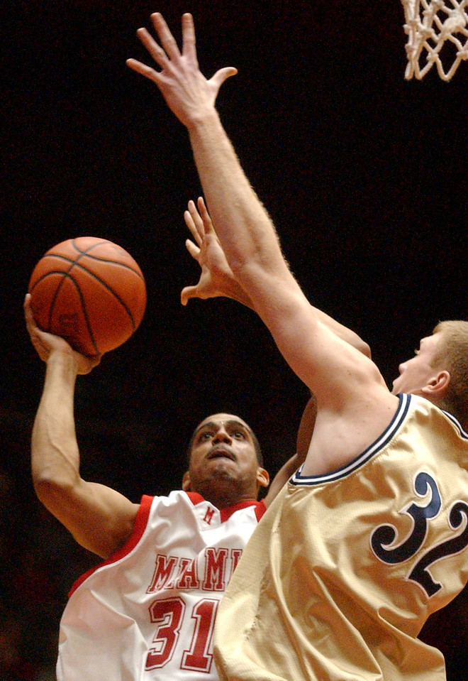 E.L. HUBBARD/JOURNALNEWS<br /> Miami forward Nathan Peavy (31) shoots while defended by Akron center Rob Preston (32) in the first half at Millett Hall Wednesday, 02/22/06.