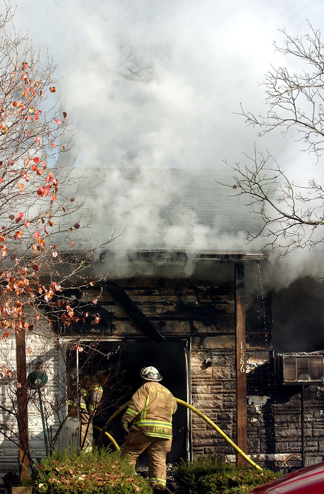 Smoke pours from the eaves of a house as a St. Clair Township((CQ)) firefighter enters the front door while battling the blaze on Wichita Dr.((CQ)) Tuesday, 11/21/06. Staff photo by E.L. Hubbard