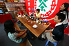 A group of people sit around chatting and drinking tea from a company in Yunnan