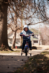 Collin Wonser, 3, rides his bike along east Magnolia Street in Independence