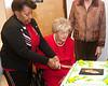 Tina Greene helps Rita De Lazzari cut the birthday cake.