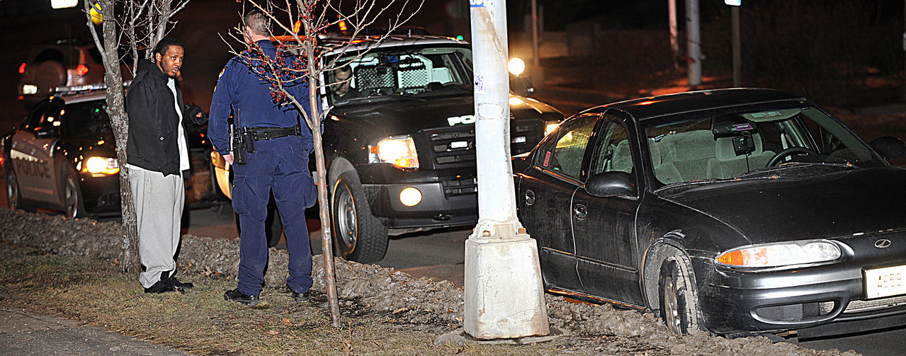 An Auburn Police officer talks with Kourtney Williams, the driver of the car at right on Main Street in Lewiston after making a traffic stop. The car was spotted heading across the Longley Bridge with a flat tire. Williams was taken into custody after he admitted he didn't have a license. Police investigated the damage to the front end of the car he was driving to see whether it matched damage to a vehicle at the scene of an assault on Winter Street that occurred shortly before Williams was stopped.