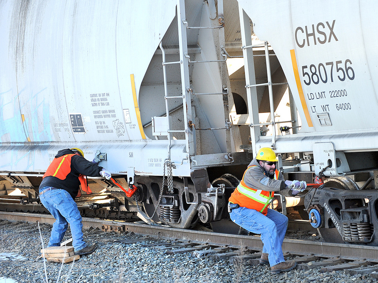 Railroad workers work to get one of 5 railroad cars back on the tracks at the Route 219 railroad crossing in Leeds early Friday morning.  Several crews, including ones from Guilford, Pan Am freight and Maine DOT were working feverishly to get the trains back on the tracks by wedging a series of wooden blocks under the wheels and inching the railroad car forward in a slow, but well practiced procedure.  There have been several derailments at this location over the past few years.