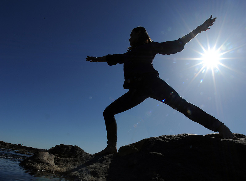 Dyan LeBourdais of Hudson New Hampshire, a yoga instructor, poses for photos on the rocks at West Pitch Park in Auburn  for her cousin Camille Cloutier of Lewiston.  The two were walking around town, taking photos and enjoying the beautiful weather.