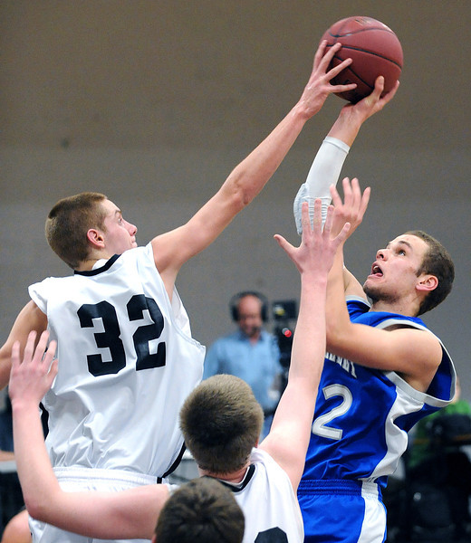 Hall-Dale's Wesley Lapointe blocks a shot by Mountain Valley's Jacob Theriault during Thursday night's boys basketball game in Farmingdale.