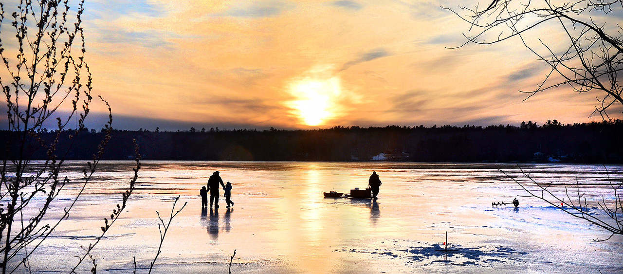 Graeme Mertens, 2, of Hollis, holds onto his fater Jared's hand with his sister Megyn, 4 as they check their ice fishing traps on Middle Range Pond with their friend Ron Davis of South Portland.