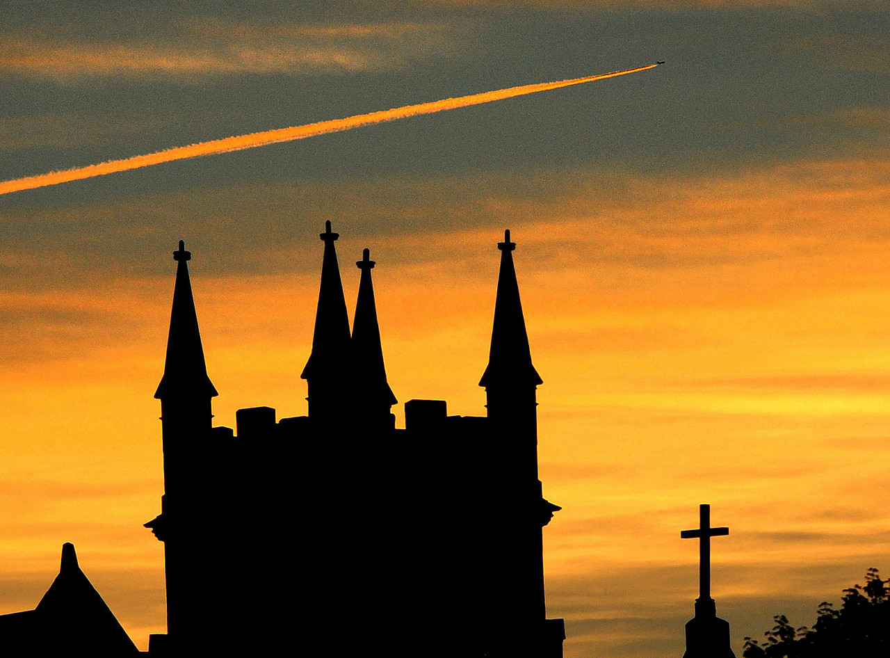 A jet streaks across the sky above the spires of St. Louis Church in Auburn Monday evening.