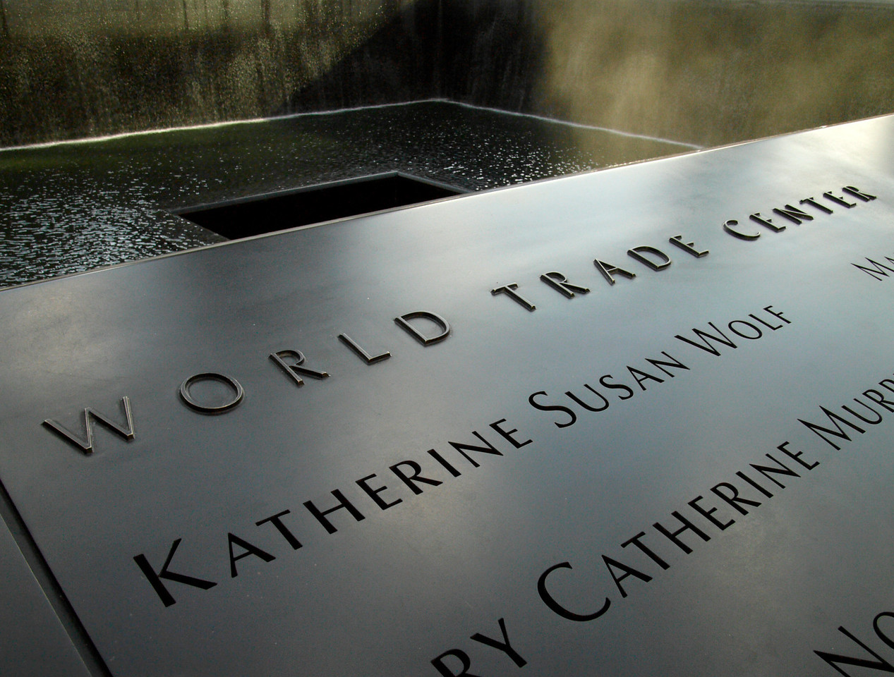 The names of almost 3000 men, women and children killed on 9/11 are etched into the bronze rim bordering each pool.