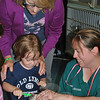 NCC director Kathy Murdy guides Sam Zavatsky, 3, in brushing Trevor's teeth, an important part of pet care, Ms Simpson told the young visitors.   (Crevier photo)