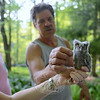 Larry Fischer points out the downy feathers on the owlet, while property owner Howard Lasher looks on.  (Bobowick photo)