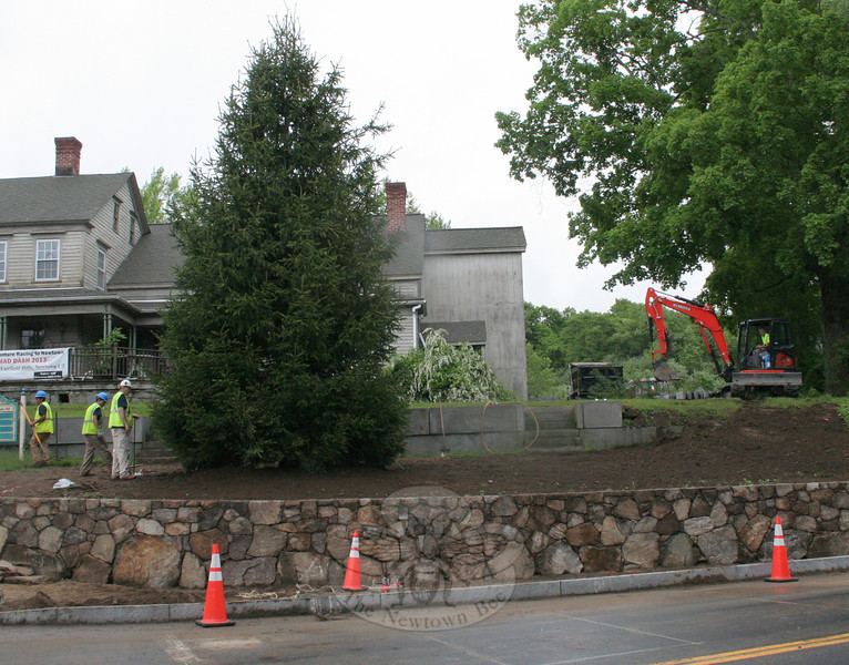 By late Friday morning, May 24, Sandy Hook Center's new Christmas tree was planted in front of 2 Riverside Road. The tree's planting was part of a large streetscape project for the intersection of Church Hill Road, Washington Avenue, Riverside Road, and Glen Road. The tree came from a farm in New Preston, and is estimated to be 20-25 years old. Workers spent nearly four hours working in the rain to make final preparations and then planted the tree, which will be the centerpiece of the business district's holiday displays for years to come.   (Hicks photo)