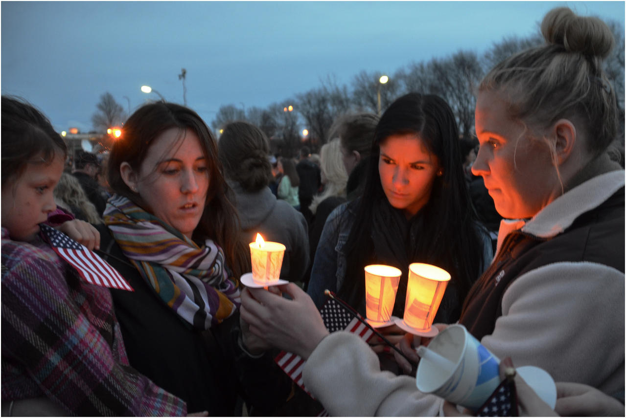 Sinead Leary, Eileen Hayes, Molly Ellis, and Genevieve Hayes huddle around candles during the vigil at Garvey Playground.
