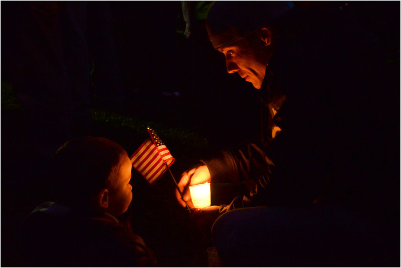 During vigil for Mark Richard, Steven Pray crouches with flag and candle next to his 20 month-old son, Steven Pray, Junior.