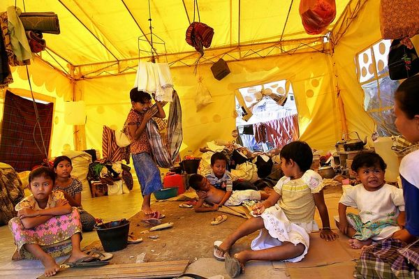 1/25/2005 -- Aceh Besar, Indonesia -- These children pass the hot daylight hours in a government-supplied, refugee tent that five families share. They are all from the same village named Lamboro Nejid, which is eight kilometers from Banda Aceh. Their homes were all destroyed by the December 26 tsunami. At the time of this photo, they were humming along to the 4:00 pm prayers broadcast from a nearby mosque. Photo by Dina Rudick, Globe Staff.<br /> <br />                              Could support stories about: dealing with health issues of refugee camps, moving forward, what went right/wrong with government responses, psychological issues and emotional fall-out<br />  in children