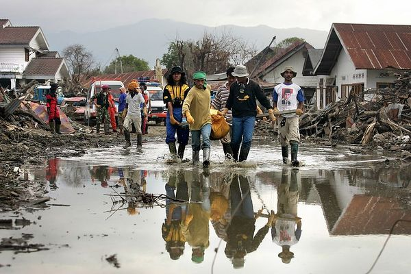 1/24/2005 -- Banda Aceh, Sumatra, Indonesia; Aceh province --  Bodies are still being discovered by the thousands each day, even a month after the December 26 tsunami. In this picture, worker haul a particularily heavy body through a puddle toward the body truck. Project on Tsunami recovery by Dina Rudick and John Donnelley. Globe Staff Photo, Dina Rudick.                                                 This may go better with the first story if it discusses removal and burial of the dead.