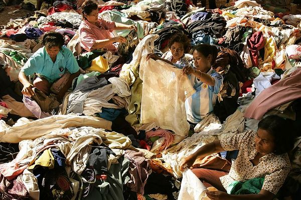 2/3/2005 -- Thailand, 1.5 hours north of Phuket -- details to come on location -- These women, living in a refugee camp 100 km north of Phuket, Thailand, sit in a veritable mountain of donated clothes that are at risk of going to waste because of infestations by vermin, insects and mosquitos. Tsunami devastated areas in Thailand have received bottlenecks of aid and lack a system of centralized organization though which to distribute it all effectively. Project on Tsunami recovery by Dina Rudick and John Donnelly. Globe Staff Photo, Dina Rudick.                   This picture directly addresses a topic of the first article.