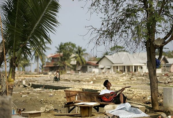 "1/23/2005 -- Sigli, Indonesia; Aceh province -- Sadikul Wahdi, 14, plays ""western music"" on his guitar to pass the time near hat was formerly the village of Basi Rawa. Project on Tsunami recovery by Dina Rudick and John Donnelley. Globe Staff Photo, Dina Rudick.                                           This picture could certainly go with the second story about looking ahead. It would support a story about psychological trauma and moving forward."