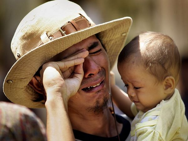 "1/25/2005 -- Banda Aceh, Indonesia -- Mohammad Budi Permana breaks down while holding a baby girl who is from his village. Permana lost his fifteen-month-old daughter, Anya, in the tsunami and has not yet given up hope of finding her, alive or dead. He asked to hold the child (Edi Mulfi) to test himself, he says. ""I though I could be the strong man,"" he later said. While he was holding Mulfi, he cried out ""I remember my daughter!"" and burst into tears. He said he previously managed to keep his emotions under control and his mind occupied in his search, but when he held the child, he lost control. He cried for a long time (20 minutes in the car); when he was composed, he brushed an eyelash that had fallen onto his left cheek, remarking, ""In Indonesia, when an eyelash falls, it means someone misses you."" He added, ""If [it falls on the] left, it means she is far...if it falls on the right, it means she is close."" He concluded, ""That means my child is alive. Somewhere.""  Photo by Dina Rudick, Globe Staff              Could accompany story about reuniting children and parents through DNA testing, emotional fallout and psychological issues."