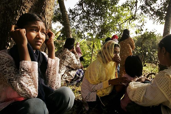 1/21/2005 -- Bande Aceh, Indonesia -- Near mass grave of 36,300 people -- Eka Riawati, 12, and her extended family, mourn their dead relatives in a small grove of trees next to a mass grave in which 36,300 people are buried. Eka's favorite aunt, Azizah, was lost in the tsunami, as were several of her other aunts and uncles. Project on tsunami recovery by Dina Rudick and John Donnelley. Globe Staff Photo, Dina Rudick.