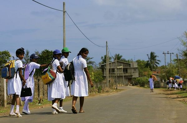 2/1/2005 -- In between Irrakkakandi and Trincomalee, Sri Lanka -- These school girls are walking home from school on February 1, 2005, along the roaside in between Irrakkakandi and Trincomalee, Sri Lanka. Project on Tsunami recovery by Dina Rudick and John Donnelly. Globe Staff Photo, Dina Rudick.                                           Would factor into second story perhaps