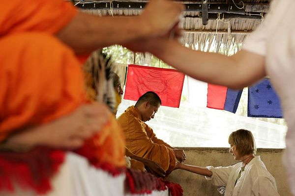 2/3/2005 -- Khao Lak, Thailand, Paul TK TK, director of construction at Tsunami Volunteer, gives a hug of farewell and appreciation to TKTK, the coordinator of all non-Thai volunteers for Tsunami Volunteer after a Buddhist blessing ceremony at the organization's headquarters near Khao Lak, Thailand.  Project on Tsunami recovery by Dina Rudick and John Donnelly. Globe Staff Photo, Dina Rudick.                   This picture directly addresses a topic of the first article.