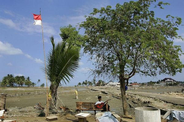 """1/23/2005 -- Sigli, Indonesia; Aceh province -- Sadikul Wahdi, 14, plays """"western music"""" on his guitar to pass the time near hat was formerly the village of Basi Rawa. Project on Tsunami recovery by Dina Rudick and John Donnelley. Globe Staff Photo, Dina Rudick.                                           This picture could certainly go with the second story about looking ahead. It would support a story about psychological trauma and moving forward."""