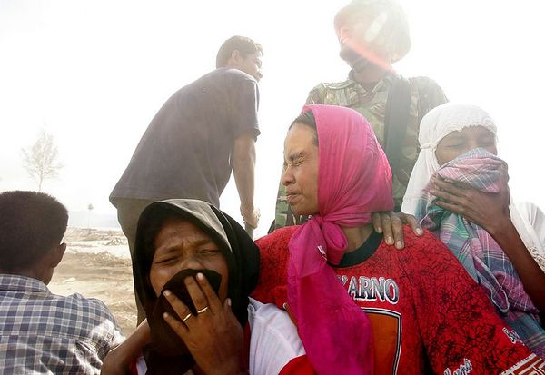 1/24/2005 -- Near the former village of Leupeung; Indonesia; Aceh province --  These women endured the long and dusty ride on the back of a truck that picked them up from a shattered roadside near what was their former home, Leupeung. The bridge to Leupeung was washed away by the December 26 tsunami, as was the villageof 12,000 residents. Only about 800 people from the village survived, and many of them return to the rubble to sleep at night even though their homes no longer stand. The Indonesian military is erecting a new bridge, though they estimate it will take a full three years to rebuild the roads in the area.  Project on Tsunami recovery by Dina Rudick and John Donnelley. Globe Staff Photo, Dina Rudick.         This photo could accompany story about what went wrong/right with the response to the tsunami -- best fit with retrospective story (first one).