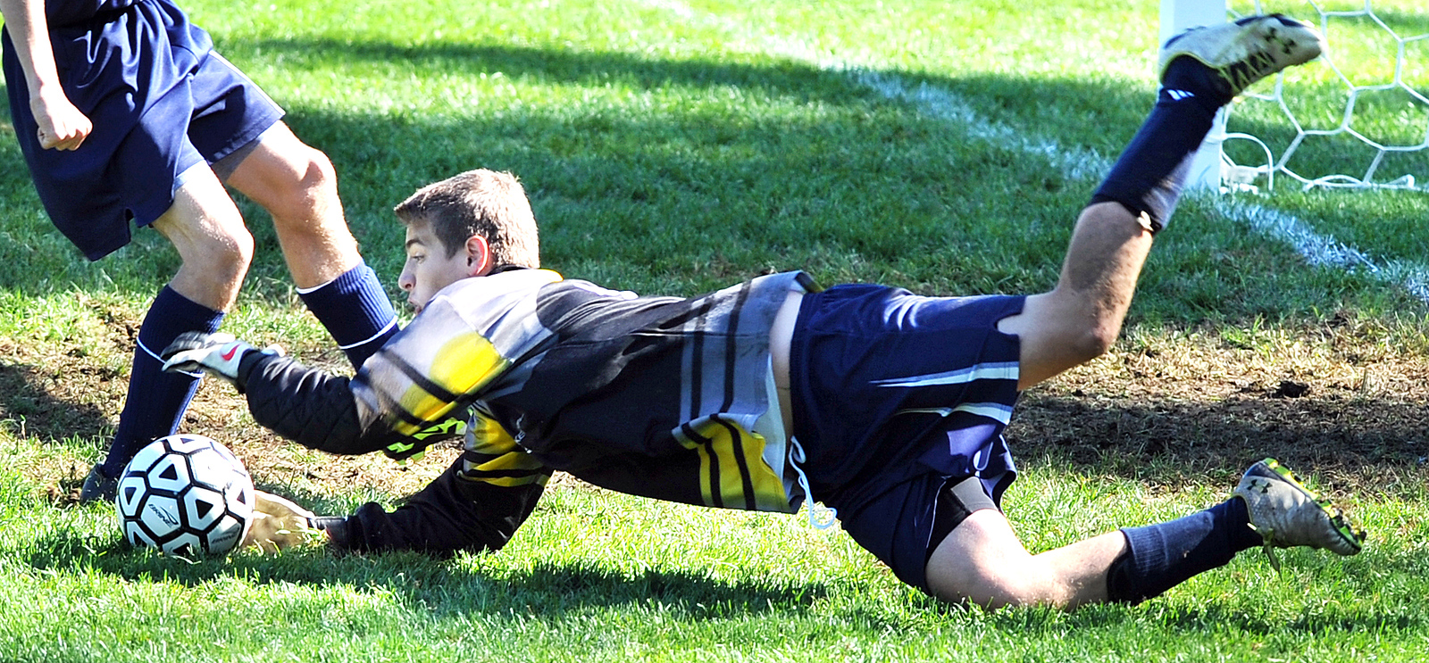 Telstar goalie Rick James dives to cover up the ball during a scramble in front of his net Saturday morning during a boys varsity soccer game against Saint Dominic Academy in Auburn.  Despite a great effort by James, the Saint Dominic team dominated the game and went on to a 7-0 victory.