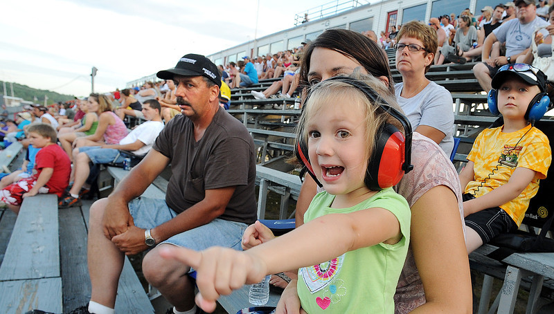 Emily Wilson, 3, of Oxford,  points to the race cars as they head to the start/finish line while sitting on her mother Regina's lap at Oxford Plains Speedway Friday night.  Her brother Nicholas, back right and grandmother Terry Hoyt.