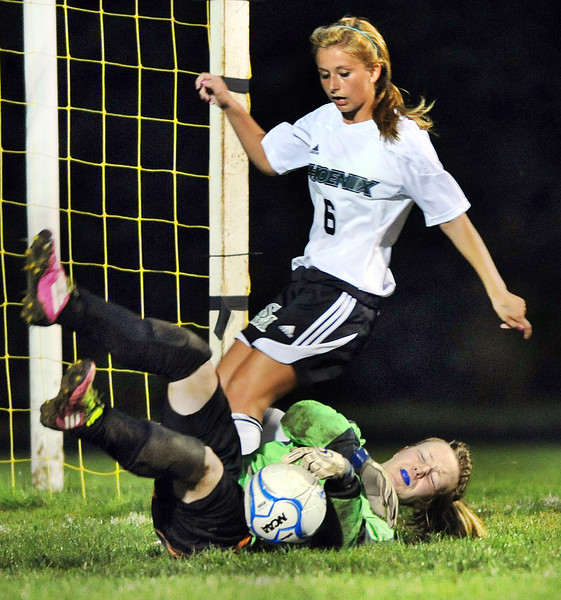 Monmouth goalie Natalie Young dives on a loose ball before Spruce Mountain's Megan Duval can get a shot off during first half action in Jay Monday night.