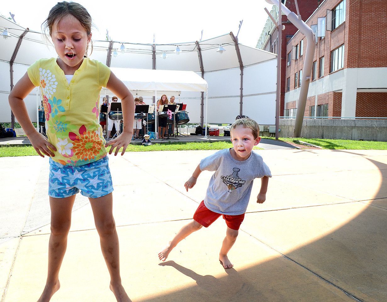 Emma Hefty, 8, and her brother Brooks, 5 of Auburn dance to the music of the Tinpanic Steel Band at Festival Plaza Thursday afternoon.  The performance was part of L/A Arts Sounds of Summer.  To watch a video from the performance, visit sunjournal.com/tinpanicsound