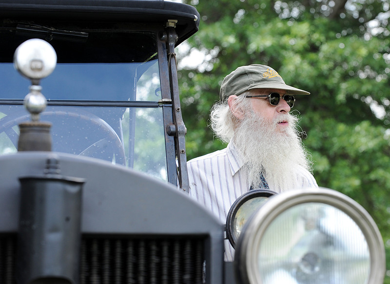 David Nergaard of Littleton, Ma. looks at other Stanley Steamers motor up to Hebron Academy Tuesday afternoon as he stands next to his 1922 Model 735 Stanley Steamer.