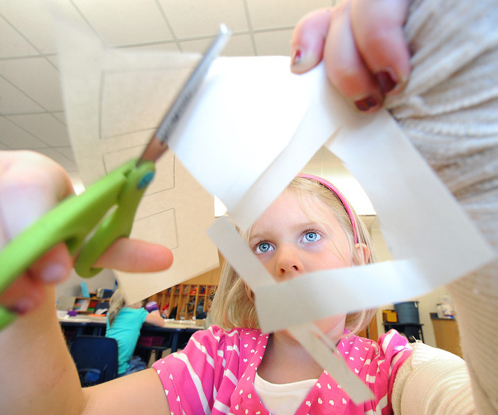 Ella Splude cuts out pieces of a paper bus she and her kindergarten classmates were making at Lisbon Community School Monday afternoon on the first day of school.