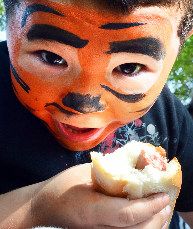 Braden Roma, 5, of Lewiston, enjoys a hot dog with his family in Kennedy Park Saturday afternoon during the block party.