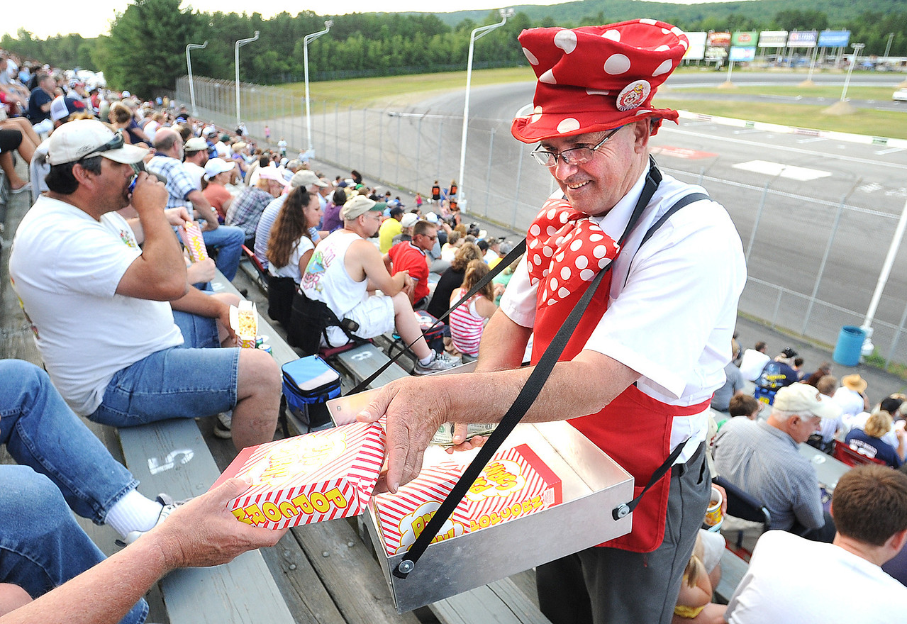Norman Jackson, aka the Candy Man, passes out popcorn in the stands of Oxford Plains Speedway Friday night.