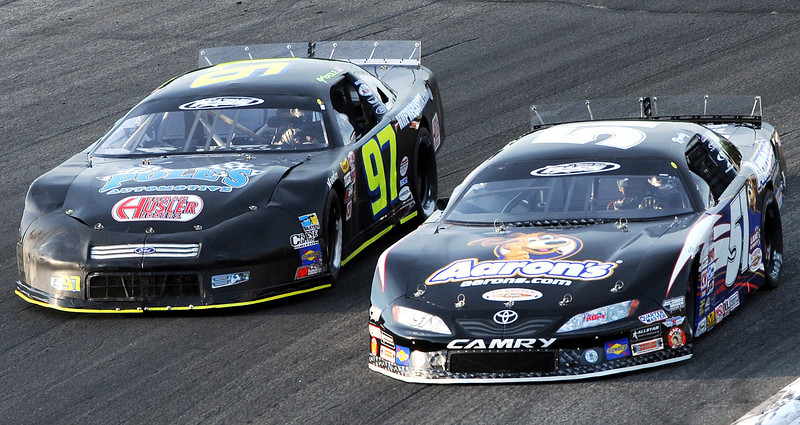 Kyle Busch, middle right, takes the inside line as he creeps up on Joey Polewarczyk, left, and passed him two turns later during Saturday night's qualifying race for the PASS North 150 Super Late Model race at Oxford Plains Speedway.  Busch won the heat.