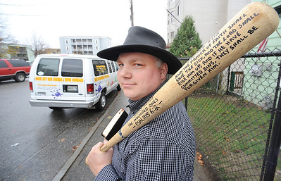 Rev. Doug Taylor keeps a bat and a bible handy to help protect him in his downtown Lewiston neighborhood.  He is standing in front of his home on Bates Street recently.