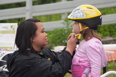 (1) Pslip Slug #: W 00019652; (2) Ridgewood, NJ; (3) 05/16/09; (4) Bike Rodeo and Safety Fair; (5) Hackensack University Hospital Trauma Prevention Coordinator & Clinical Educator Meliam Gonzales, R.N., adjusts Hannah Clay's new bicycle helmet at the Ridgewood Bike Rodeo on 5/16/2009; (6) W.H. Grae for the Ridgewood News.