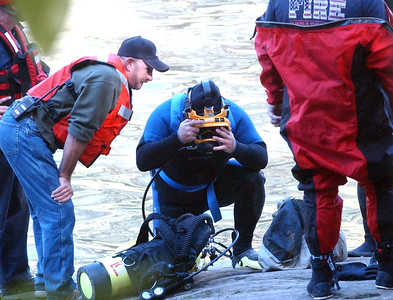 A diver prepares to enter the Black River at East Falls in a river rescue attempt after a boy fell in Oct. 10. Steve Manheim / Chronicle