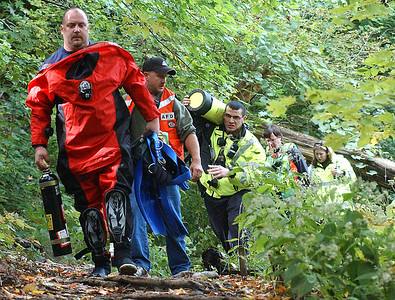 Firefighters scale the trail  with equipment to approach East Falls in a river rescue attempt Oct. 10. Steve Manheim / Chronicle