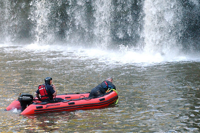 Elyria firefighter Dean Marks, at front of boat, works in a river rescue effort after a boy fell from a cliff at East Falls on Oct. 10. Steve Manheim / Chronicle