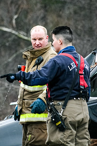 Fire fighters and EMTs inspect a rolled pickup truck at the corner of Maguire Rd. and Hartwell Ave. in Lexington, MA.