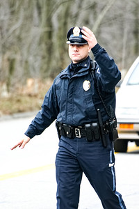 A police officer directs traffic at the corner of Maguire Rd. and Hartwell Ave. in Lexington, MA.