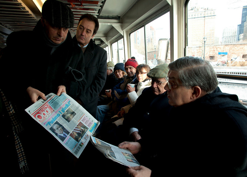 (L-R): Msgr. Gennaro Matino, Hon. Vincenzo Scotti and Cardinal Sepe read the daily newspapers on the ferry to the Immigration Museum at Ellis Island. <br /> New York, January 20th, 2011